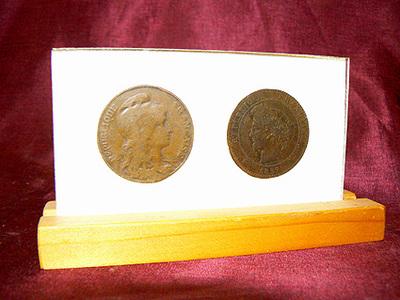 2 Franse munten welke zijn gevonden in de Franse danspiano, de Cleophas Tricart. 1 Munt is van 1897, waarde 10 centimes, 1 munt is van 1900, waarde 10 centimes, beide in lijst op voetstuk.