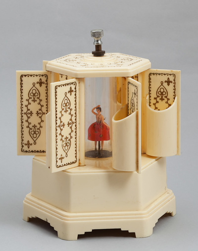 Cilinderspeeldoos van plastic, zeshoekig met daarop klein zeshoekig prieel waaraan schanierende panelen met half ronde bakken, in het midden een danseres. Vervaardiger Reuge Zwitserland, omstreeks 1950.