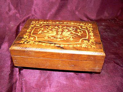 Rechthoekige doos met scharnierend deksel, op deksel inlegwerk van hout voorstellende 2 tegenover elkaar staande draken, geheel omkaderd. In doos ruimte voor kleine spullen. Het mechaniek zit rechts maar de kam mist 4 tanden. Vaste opwindsleutel onderaan de doos.
