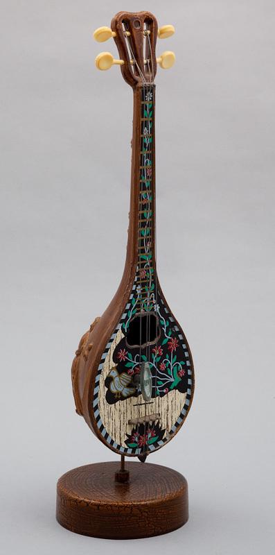 Cilinderspeelwerk voorstellende een Grieks snaarinstrument. Het instrument draait tijdens het spelen van de melodie rond. Achter op de bolle kast is een dansende man en vrouw in griekse klederdracht uitgesneden. De achterkant van de steel stelt een bloemenrank voor. De voorkant is beschilderd met bloemen. Links van het midden van de kast is een vogel afgebeeld. Datering 1950-1980.