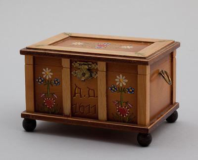 Cilinderspeeldoos in de vorm van een dekenkist, aan zijkant twee ronde ringen van metaal. De voorkant van de kist is in drie vakken verdeeld, welke links en rechts beschilderd zijn met bloemen, in het middelste vak 'A.D. 1611', de melodie is 'Der Reigen'. Vervaardiger door Reuge Zwitserland.