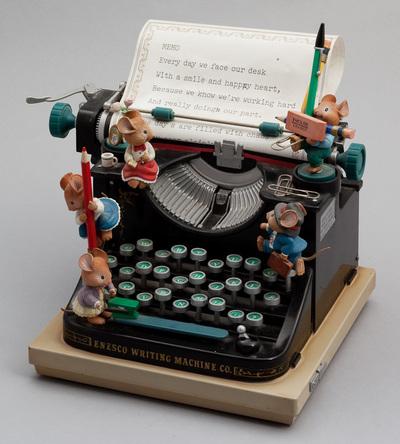 Typemachine met speelwerk gaat elektrisch, op de machine zijn diverse muizen met o.a potloden, nietmachine e.d. aangebracht, ook een vel papier met tekst. Vervaardiger Enesco China, datering 1980-1990.