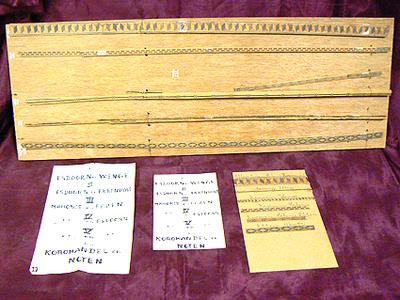 Plank triplex waarop 6 soorten hout zijn ingelegd als voorbeeld voor het houtwerk van de speeldozen. 1-Esdoorn/Wenge; 2-Esdoorn/Ebbenhout; 3-Mahonie/Ebben; 4-Mahonie/Esdoorn; 5-Mahonie-Esdoorn; 6-Koromandel/noten.