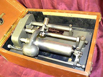 Dictaphoon dicteermachine.Rechthoekige kist met deksel waaraan 2 klipsluitingen, de dictaphoon of opnameapparaat in de kist. Vervaardiger Ediphoon, datering 1910.