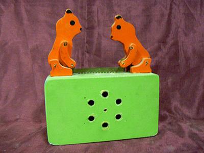 Rechthoekige houten groene doos met zes gaten in front, twee houten bruine dieren bovenop die bij het draaien van de zwengel (achterzijde) gaan zagen. Daarmee gaat ook het speelwerk spelen. Datering 1965.