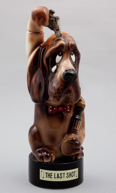 Beeld van aardewerk, voorstellende een hond voorzien van een fles en revolver. Op de voet de titel van het lied: The last shot. Speelwerk wordt geactiveerd bij het optillen van de fles. Datering 1950.