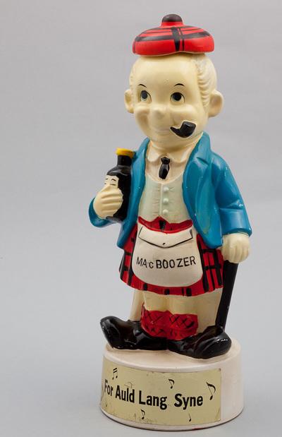 Beeld van aardewerk, voorstellende een Schotse man. Tekst op schort: Mac Booze. Lied is: For auld lang syne. Speelwerk wordt geactiveerd bij het optillen van het beeld. Datering 1950.