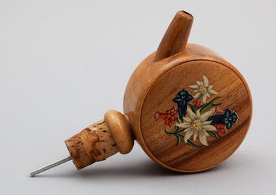 Ronde schenktuit van hout met speelwerk, waarbij op de onderzijde kurk om op flessenhals te klemmen. Voorzijde een afbeelding van bloemen. Bij niet horizontale houding gaat het muziekwerk spelen, melodie 'Geef me nog een druppie'. Datering 1950.