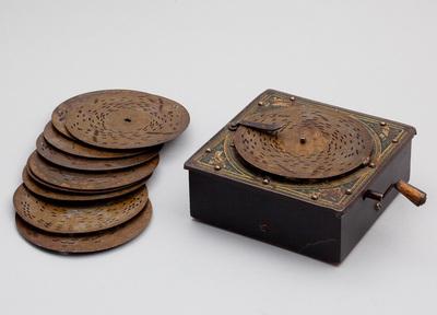Houten schijven speeldoos met metalen bovenblad welke is versierd. Toonkam heeft 20 tanden. Aan de zijkant het draaimechanisme, knop kan eraf. Op de onderzijde staat 'Ehriichs Patent'. In totaal zijn er 10 schijven van 9.5 cm doorsnede. Datering 1920.