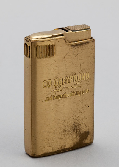 Metalen aansteker met speelwerk. Aan achterzijde opwindsleutel, voorzijde tekst 'Go Greyhound . . . and leave the driving to us'. Onderzijde 'Pacton Musical 18K Gold Plated Japan'. Datering 1950.