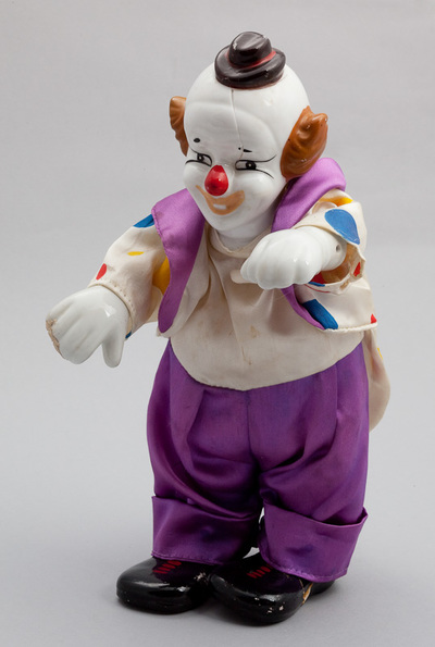 Clown pop met daarin een mechanisch speelwerk. Opwindmechanisme aan de achterzijde, bovenlijf van de clown beweegt op de muziek. Datering 1960.