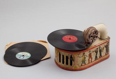 Speelgoed pathofoon gemaakt van blik. Daarbij zijn 22 bakelieten platen van verschillend formaat. Los daarbij een kleine metalen doos met als inhoud een aantal naalden voor deze pathofoon. Tevens een klein boek (losse vellen) met liederen. Datering 1930.