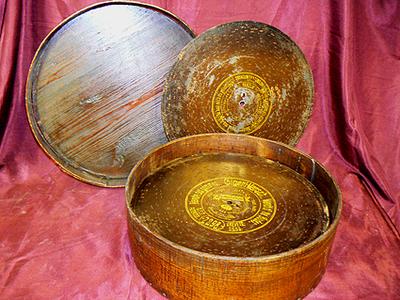 Ronde metalen schijven voor speeldoos. Alle 30 opgeborgen in een ronde houten doos met afsluitbaar deksel. Datering 1930.