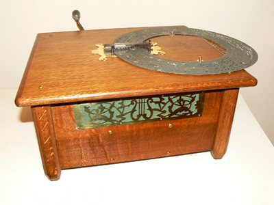 De Ariosa II is van Duitse makelij, omstreeks 1880. De speeldoos heeft een balg en 18 toontongen. Het bijzondere is dat de schijf boven op de kast door een loopwerk draait. Een slinger drijft het loopwerk en de balg aan. In de openingen van de schijf vallen pennen die via hefbomen de kleppen openen, waardoor de wind uit de balg door de toontongen kan gaan, welke de melodie voortbrengen. Deze speeldozen waren de goedkopere voorlopers van de meer bekende schijvenspeeldozen die een toonkam hebben.