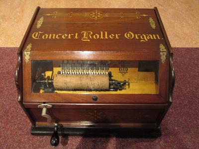 Cilinderorgel met opschrift Concert Roller Organ. In het orgel zit een kleine cilinder met pinnen die de tongen bespeelt. Door handmatig draaien wordt de cilinder bewogen en lucht naar de kleppen gepompt.