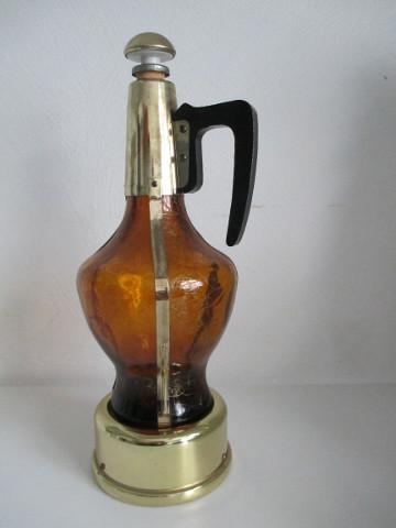 Karaf gedeeltelijk van bruin glas gedeeltelijk van messing met een speelwerk ingebouwd voorzien van aangezet handvat en druppelaar in de losse dop