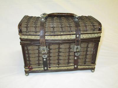 kleur; bruin, stof met riet gevlochten in ruitpatroon, 2hengsels met metalen ringen en metalen ronde pootjes, houten bodem, leren banden met metaten knipsluiting