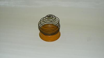 Metalen komvoet waarin een bol wol kan worden gelegd. Aan de voet een uitklapbaar metalen spiraal waardoor de woldraad kan.