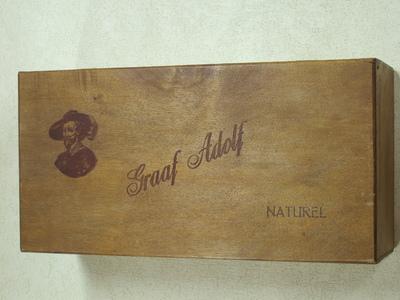Rechthoekige kist met op het deksel een afbeelding van een borststuk van een ouderwets geklede figuur met baardje en hoed. Opschrift in schrijfletters 'Graaf Adolf' en in blokletters 'Naturel'.