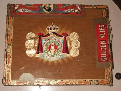 Sigarenkist van hout, gedeeltelijk beplakt met gekleurd papier. Op deksel drie etiketten.