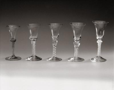 Kelkglas op conische voet met brede, neerwaarts omgeslagen rand. Geribde, gedraaide stam. Klokvormige kelk met onderaan een massieve knoop en bovenaan een iets naar binnen buigende mondrand. (afb. 1e van links)