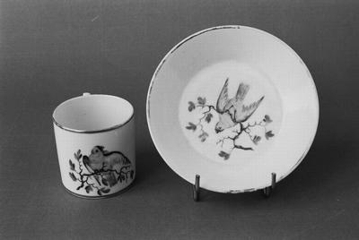 Kop en schotel. Amstel-porselein, waarschijnlijk uit de Dommer-periode: 1800 tot ca. 1814. Hoort bij twee andere koppen en schotels zonder nummer (T 00105 en T 00107). Het decor is verwant aan het servies GM 10427 (1-53).