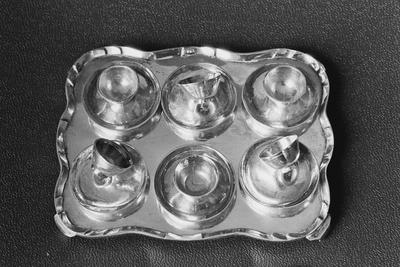 Zilveren schoteltje in miniatuur, behorend bij een theeservies met zes kopjes en schoteltjes op een dienblad. De vorm van de schoteltjes is rond en licht gewelfd op een lage standring.