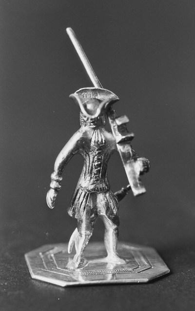 Staande soldaat van zilver in miniatuur met musket. De soldaat staat op een vierkant grondje met afgeschuinde hoeken. Hij draagt een zwaard en musket over de linkerschouder. Op het grondje is een band gegraveerd.