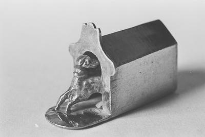 Zilveren kinderspeelgoed met als voorstelling een hond in een hok in miniatuur. Het hondehok is rechthoekig van vorm met een puntdak en een geprofileerde kuif. De bodem is verlengd met een halfrond grondje. Daarop de half uit het hok staande hond.