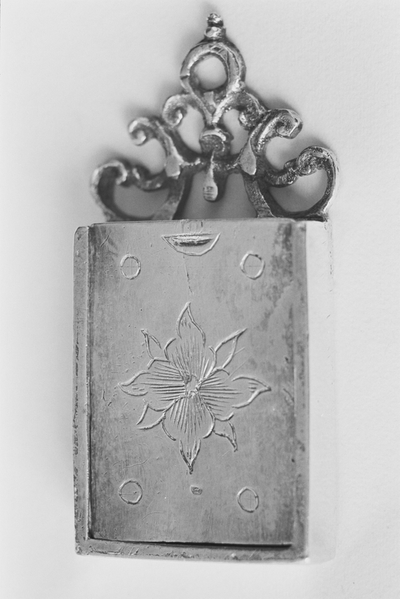 Rechthoekige zilveren schooltas in miniatuur met schuifdeksel. Het schuifdeksel is bekroond met een symmetrisch ornament. Op het deksel is een bloem gegraveerd en in de hoeken vier cirkels.