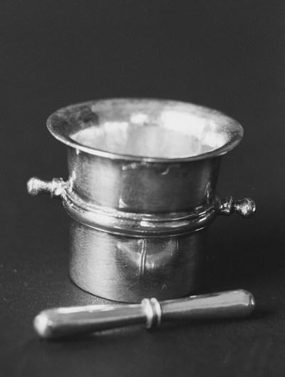 Zilveren vijzel met stamper in miniatuur. De zilveren vijzel is bekervormig met een buitenwaarts geboden monding en een geprofileerde band over het midden met twee knopvormige handgrepen. De stamper is dubbel knotsvormig.