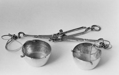 Zilveren balans in miniatuur. De gelijkarmige balans heeft aan beide armen drie touwtjes en een wijd convex trechtervormig bakje.