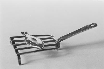 Zilveren kinderspeelgoed in de vorm van een bakroostertje in miniatuur, met vijf spijlen op drie poten aan een schuin omhoogstaande steel met een druppelvormige opening. Op het rooster is in reliëf een vis afgebeeld.