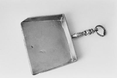 Klein stofblik van zilver in miniatuur. Het blikje is rechthoekig, iets wijd uitlopend en heeft drie opstaande randen. De steel is geprofileerd met een vast en daarin een los oog.