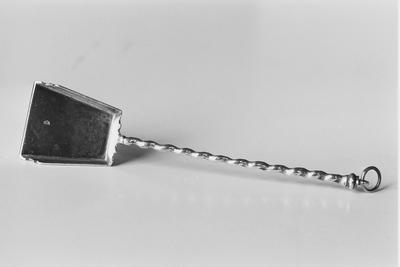 Zilveren haardschepje in miniatuur. Het schepje heeft een wijduitlopend blad met schuin opstaande randen die aan de voorzijde schuin geprofileerd eindigen. De opstaande rand aan de achterzijde is gekarteld. De getordeerde steel eindigt in een geprofileerde knop met een vast oog en daarin een los oog.