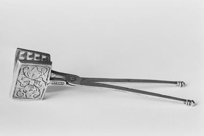 Zilveren wafelijzer in miniatuur, bestaande uit twee rechthoekige platen met een symmetrisch rank- en bladmotief, bevestigd aan twee lange scharnierende handgrepen met geprofileerde knopjes.