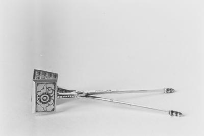 Zilveren wafelijzer in miniatuur, bestaande uit twee rechthoekige platen aan twee lange scharnierende handgrepen met geprofileerde knopjes. Op de platen is een gestileerde bloem gegraveerd.