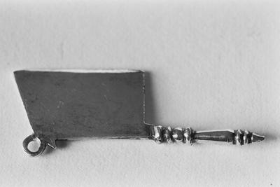 Zilveren hakmesje in miniatuur. Het mes is rechthoekig van vorm met een scherphoekig einde. Aan de bovenzijde van het mes zit een oogje. De handgreep is geprofileerd.
