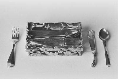Zilveren bestekbakje in miniatuur, gevuld met vijf vorken, zeven lepels en zes pistoolmessen. Het bakje is rechthoekig, het heeft drie smalle vakken en opstaande s-vormig gebogen opengewerkte wanden in een ajour ranken motief. De vorken en lepels hebben spatelvormige heften met een verdikking over de lengte-as.