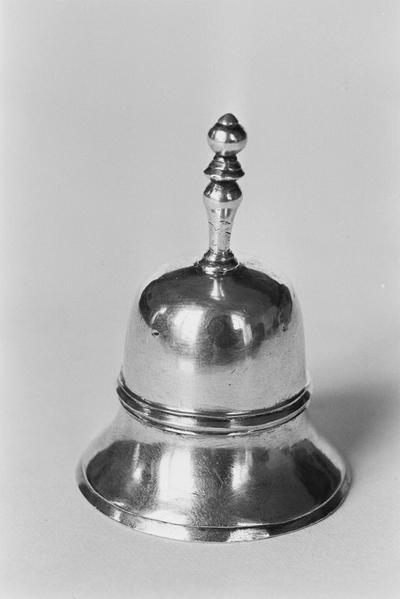 Zilveren tafelbel in miniatuur. De bel is klokvormig met een geprofileerde steel. De klepel is knotsvormig en met een achtvormige schakel aan de bel verbonden.