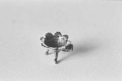 Zilveren pijpenkomfoor in miniatuur. De vorm is halfbolvormig op drie pootjes met geschulpte rand en een cilindrische holle steelhouder. De steel ontbreekt.