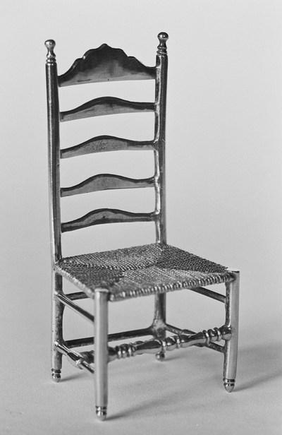 Zilveren stoeltje in miniatuur; 17e eeuws model. De stoel heeft een rechte rugleuning en rechte poten. In de rugleuning zitten vijf gebogen horizontale spijlen. De zitting heeft een vlechtmotief. Tussen de poten twee geprofileerde dwarsspijlen en vier gladde spijlen.
