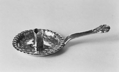 Zilveren blaker in miniatuur. De blaker is rond van vorm met een schuinoplopende naar buiten gebogen belobde rand. In de bodem een bladmotief. De kaarshouder heeft een afgeronde ingesneden monding. Aan de blaker een platte schuinoplopende steel eindigend met een rond gat in een breder bladmotief.