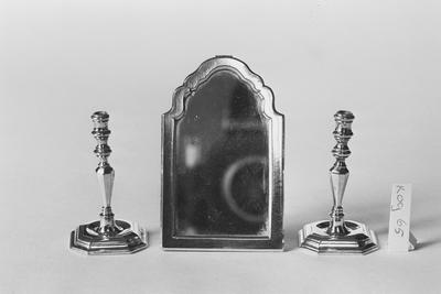 Zilveren kandelaar in miniatuur, met vierzijdig geprofileerde voet met afgeschuinde hoeken en een iets verdiept middendeel. De schacht is gefacetteerd knotsvormig, overgaand in twee geprofileerde nodi, bekroond door een geprofileerde kaarsenhouder.