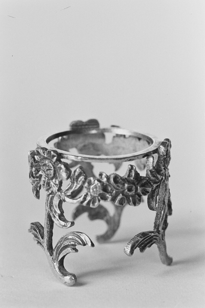 Zilveren zoutvaatje in miniatuur, met een rand van bloemmotieven op drie bloemstengels gemonteerd op een cirkelvormige platte ring. Het glazen binnenbakje ontbreekt.