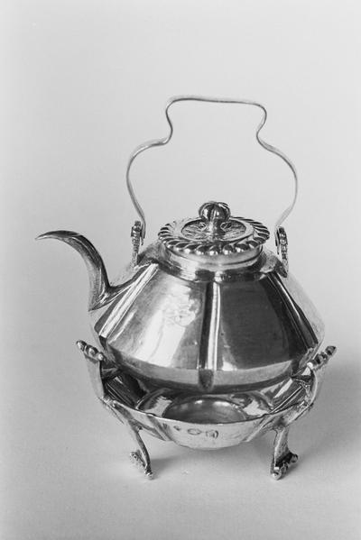 Zilveren waterketel in miniatuur, behorend bij komfoor KOG 72-1. De ketel is conisch van vorm met zes verticale gleuven en een gewelfde bodem en een inspringende cilindrische hals. Het scharnierende hengsel is meervoudig gebogen. De tuit is gebogen van vorm met een smalle lip. Het platte deksel heeft een gedreven versiering en geschulpte rand op een inspringende cilindrische ring en een platronde zesvoudig ingesneden knop.