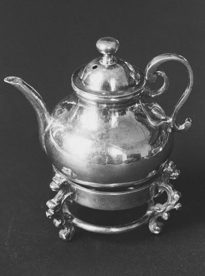 Zilveren theepot in miniatuur, behorend bij komfoor KOG 73-1 (kinderspeelgoed). De theepot is breed omgekeerd balustervormig van vorm met een flauw gebogen tuit. Het deksel is wijd klokvormig met een inschietende cilindrische ring en een platronde knop. Het oor van de theepot is staand en grillig s-voluutvormig.