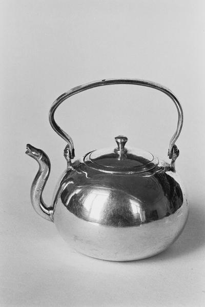 Zilveren waterketel in miniatuur. De ketel is samengedrukt bolvormig met een s-vormige tuit en een staand scharnierend deksel. Het platronde deksel heeft een knopje.