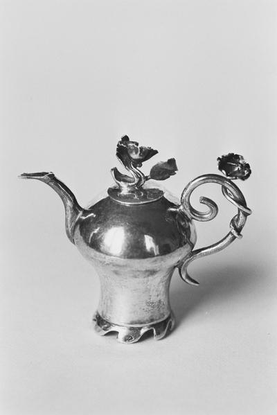 Zilveren theepot in miniatuur. De kan is balustervormig op een convex-conische standring met golfpuntrand. Het losse deksel is vlak met een invallende sluitrand en een bloemvormige knop. De kan heeft een staand s-vormig, met een bloem omrankt oor en een flauw s-vormig gebogen tuit.
