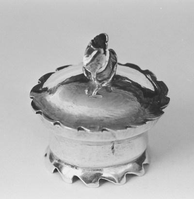 Zilveren terrine met deksel in miniatuur. Het bakje is ovaal omgekeerd conisch ingesnoerd op een convex-conische voet. Langs de standring en langs het deksel een golfpuntrand. Het deksel is flauw gewelfd met een invallende sluitrand en een bladvormige knop.